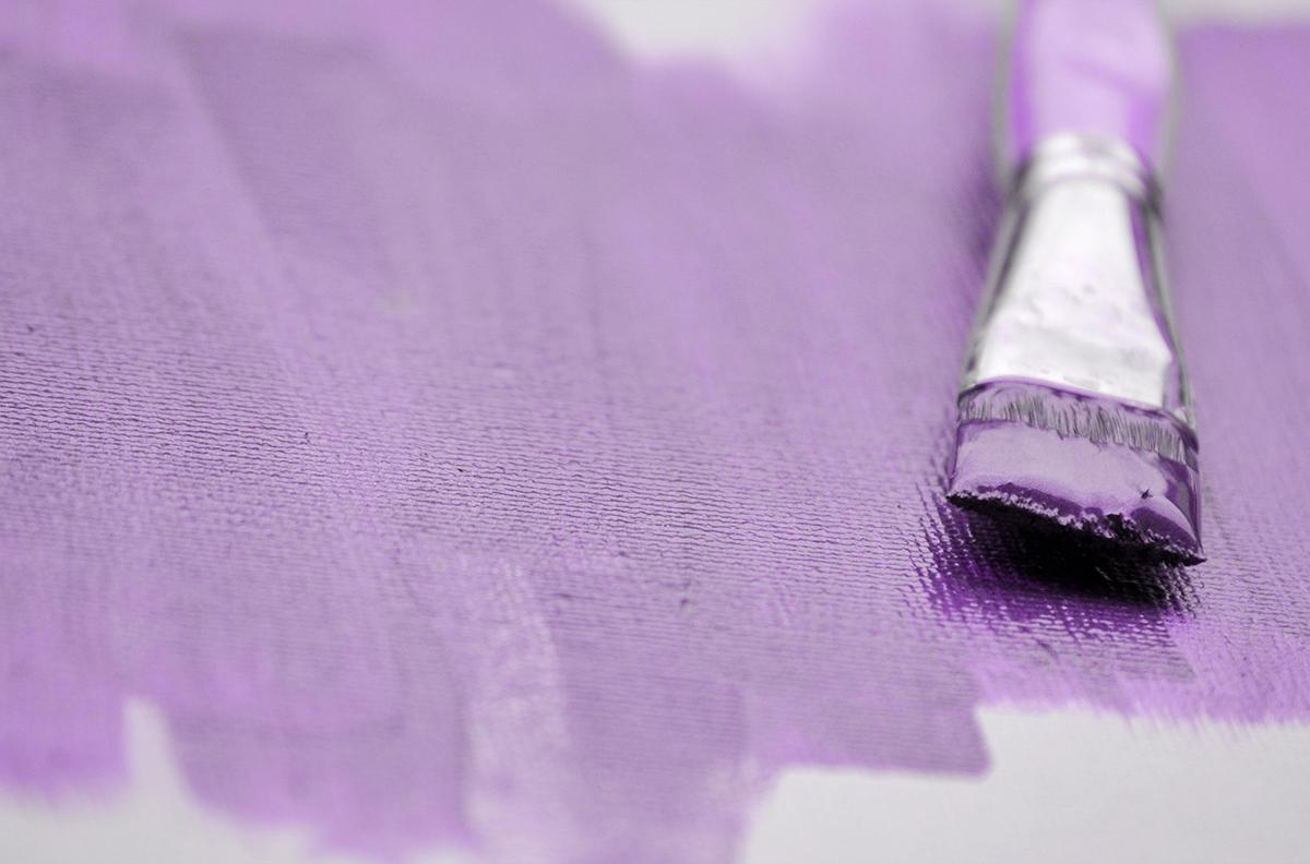 détail toile de peinture avec un fond violet avec pinceau posé dessus