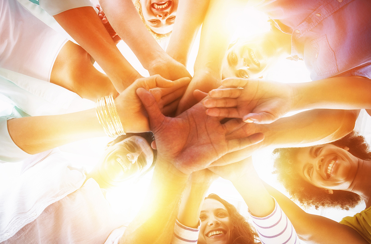 groupe de personnes empilant leurs mains les unes sur les autres en signe de cohésion